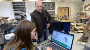 Paleontologist Dr. Kenneth Lacovara reviews digital 3D scans of Dreadnaughtus with student Emma Fowler.
